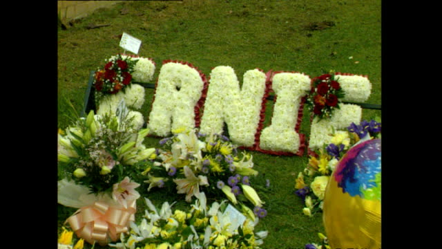 exterior shots of flowers being laid outside slough crematorium for the funeral of ernie wise, including notes of sympathy from various celebrities... - 俳優 ロジャー・ムーア点の映像素材/bロール