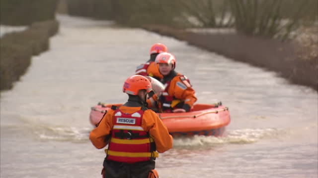 exterior shots of food boxes & search & rescue team using inflatable boats to distribute food to those affected by floods. all major roads into... - somerset england stock videos & royalty-free footage