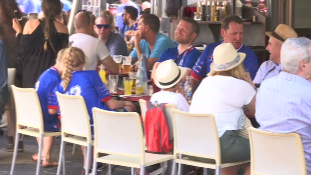 vídeos de stock, filmes e b-roll de exterior shots of football fans wearing iceland and england football shirts sitting outside bars and cafes in nice >> on june 27 2016 in nice france - euro 2016