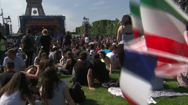 Exterior shots of football supporters at a Euro 2016 fan zone near the Eiffel Tower including people taking selfies and wearing their country's flags...