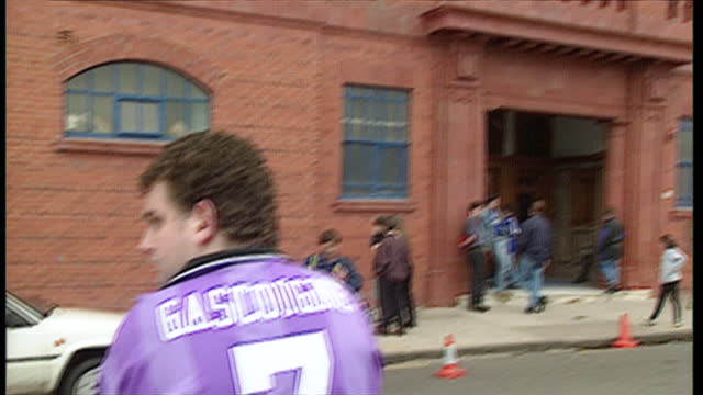 vídeos de stock, filmes e b-roll de exterior shots of footballer paul gascoigne signing autographs for fans at ibrox stadium after signing for the club on july 10 1997 in glasgow... - liga esportiva