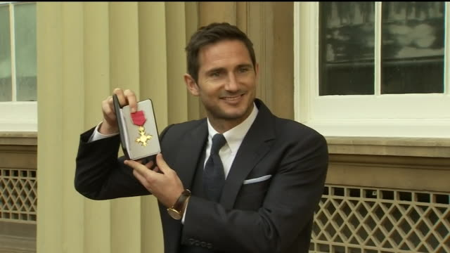 exterior shots of former england international and chelsea footballer posing for photos with his obe alongside his wife christine lampard at... - christine bleakley stock videos & royalty-free footage