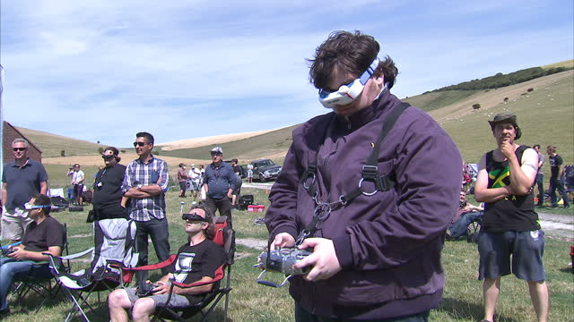 Exterior shots of FPV Drone Racing showing various people wearing video googles and using a remote control to fly drones around a course on July 18...