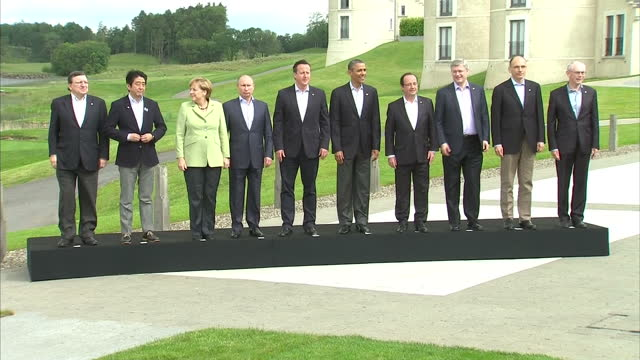 exterior shots of g8 leaders walking up onto podium to pose for photo op pans across leaders before they turn around and walk off world leaders come... - g8 summit stock videos & royalty-free footage