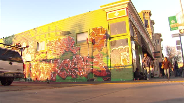 vídeos de stock, filmes e b-roll de exterior shots of general life around the mission area of san francisco as commuters walk to work including a homeless man at the side of the road... - mural objeto manufaturado