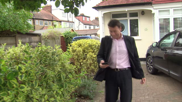 Exterior shots of General Secretary of the Labour Party Iain McNichol MP departing his house and ignoring questions from journalists on August 11...