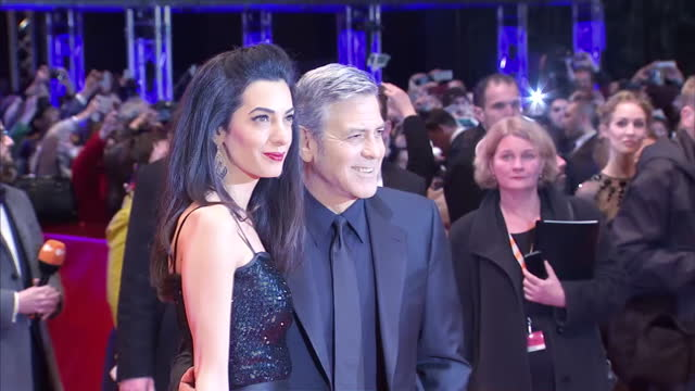exterior shots of george clooney with wife amal clooney, latter with ethan coen, posing for photo op on red carpet at the premiere of his new film... - ジョージ・クルーニー点の映像素材/bロール