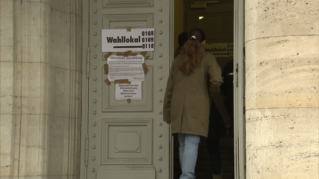 exterior shots of german people walking in and out of a town hall polling station voting in regional elections widely seen as a test for chancellor... - wahlurne stock-videos und b-roll-filmmaterial