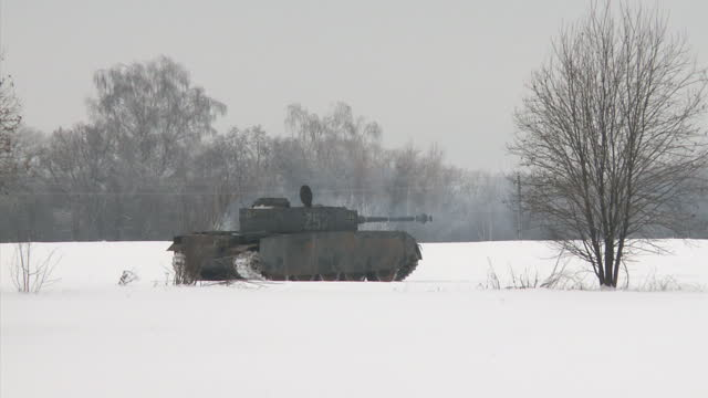 exterior shots of german world war two tanks driving and people in replica uniforms taking part in a reconstruction of a ww2 battle in the snow in... - armoured vehicle stock videos & royalty-free footage