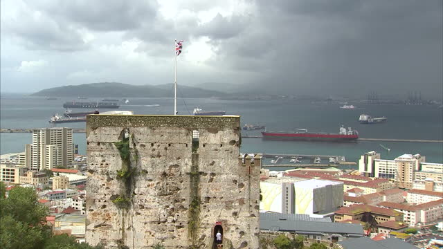 Exterior shots of Gibraltar's old fortified walls with a Union Jack flag flying on top and rootops and port activitiy in the background on May 19...