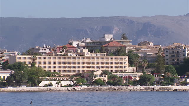 exterior shots of govino bay and rows of hotels and apartments with mountains behind on may 23 2015 in corfu greece - carbon monoxide stock videos & royalty-free footage