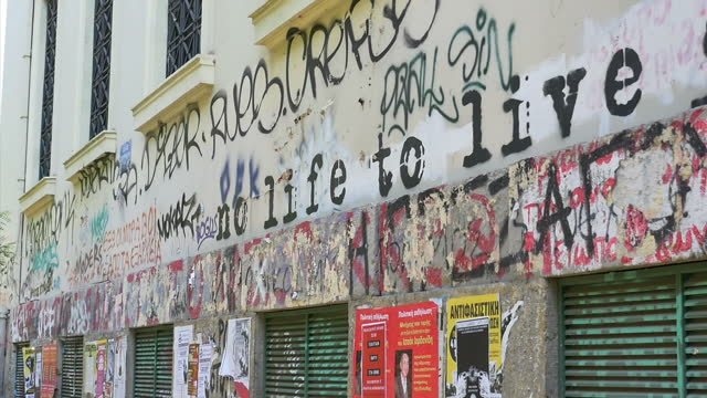 exterior shots of graffiti on a run down building in athens reading 'the future is now' on june 05 2015 in athens greece - rezession stock-videos und b-roll-filmmaterial