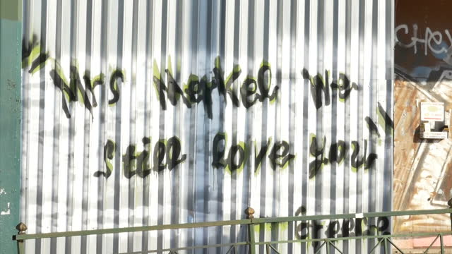 exterior shots of graffiti on a wall in athens reading 'mrs merkel we still love you greece' on june 05 2015 in athens greece - 緊急援助点の映像素材/bロール