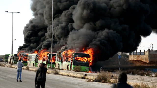 stockvideo's en b-roll-footage met exterior shots of green evacuation busses on fire with thick plumes of smoke billowing from it on december 19 2016 near idlib syria - midden oosten
