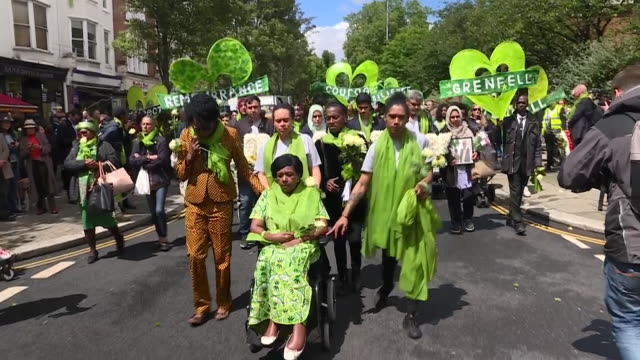 stockvideo's en b-roll-footage met exterior shots of grenfell survivors bereaved and supporters releasing green balloons into the sky and taking part in a silent march wearing green... - stille