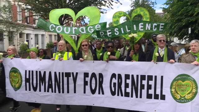 stockvideo's en b-roll-footage met exterior shots of grenfell survivors bereaved and supporters taking part in a silent march wearing green and taking part in a silent vigil on 14 june... - stille