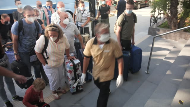exterior shots of groups of german tourists disembarking a tui coach with luggage and waiting to check into a riu hotel on arrival on mallorca on... - majorca stock videos & royalty-free footage