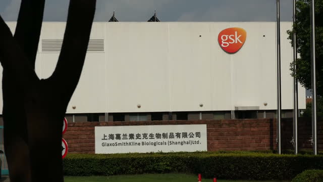 exterior shots of gsk, flag of china & union jack flag,sign at the entrance to glaxosmithkline factory, and wide shots of the factory with a gsk sign... - pharmaceutical manufacturing machine stock videos & royalty-free footage