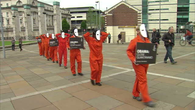 exterior shots of guantanamo bay protesters marching along street in belfast wearing orange jump suits prisoner suits holding placards and signs... - prisoner orange stock videos & royalty-free footage