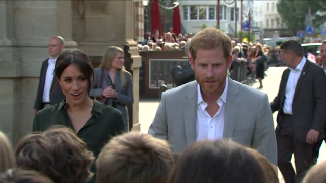 vídeos de stock, filmes e b-roll de exterior shots of harry and meghan the duke and duchess of sussex walk up to a group of school children and ask them where their school is outside... - realeza britânica
