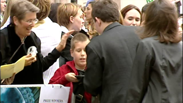 vídeos de stock e filmes b-roll de exterior shots of harry melling signing autographs at the premiere of harry potter and the prisoner of azkaban. on may 30, 2004 in london, england. - autografar