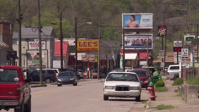 exterior shots of hazard main street with a stars and stripes flag flying various businesses and cars passing on 20 april 2017 in hazard kentucky - ケンタッキー州点の映像素材/bロール