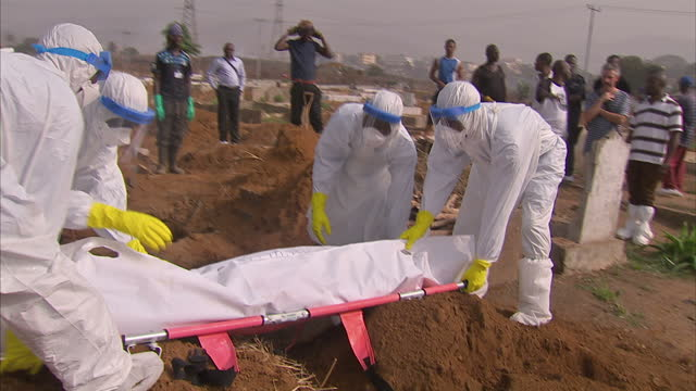 vídeos y material grabado en eventos de stock de exterior shots of healthcare workers or volunteers in a remote part of sierra leone unloading the body of an ebola victim from an ambulance and... - ébola