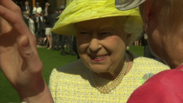 exterior shots of Her Majesty Queen Elizabeth II wearing a canary yellow jacket and hat meeting guests at Royal Garden Party including long medium...