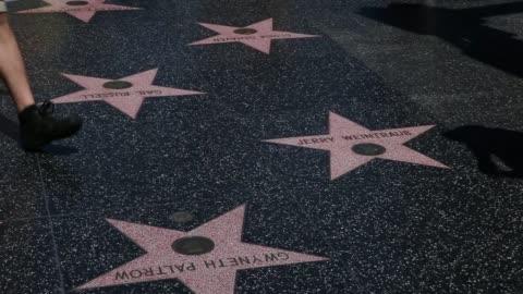 vídeos y material grabado en eventos de stock de exterior shots of hollywood boulevards walk of fame stars and cement panels, tourists walk along the walk of fame path stepping over stars of john... - paseo de la fama