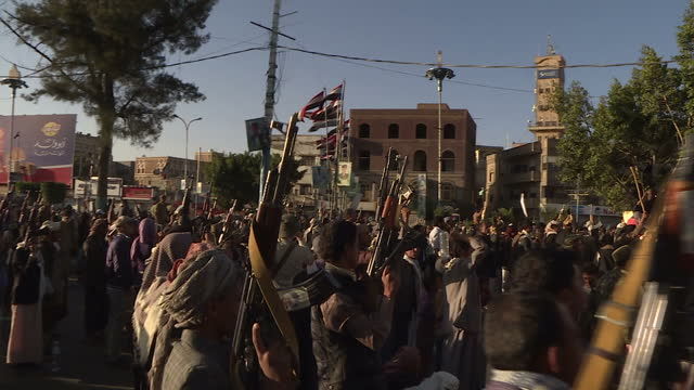 Exterior shots of Houthi supporters chanting in square whilst holding up their weapons on December 13 2016 in Sana'a Yemen