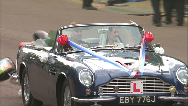 exterior shots of hrh prince william catherine duke duchess of cambridge drive away in a newlyweds decorated aston martin car after their wedding... - ウィリアム王子点の映像素材/bロール