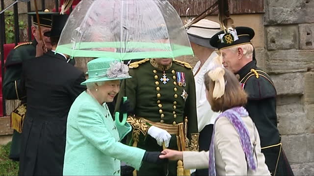 exterior shots of hrh the queen shelters from the rain under an umbrella while hosting a garden party in the gardens at buckingham palace hrh queen... - inchinarsi video stock e b–roll