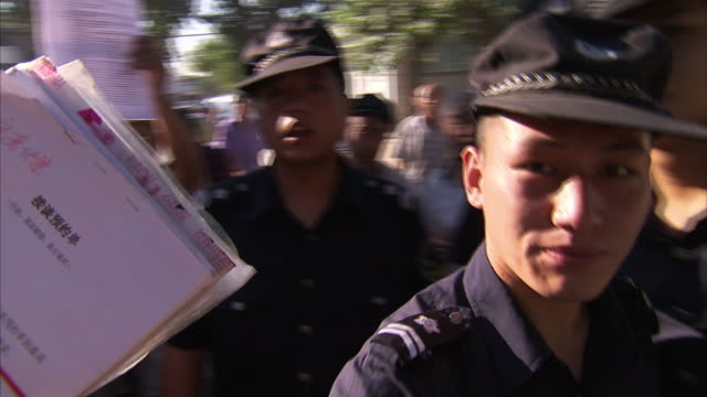 Exterior shots of hundreds of Chinese citizens queued outside the Supreme court waiting for their cases to be heard holding their documents Police...