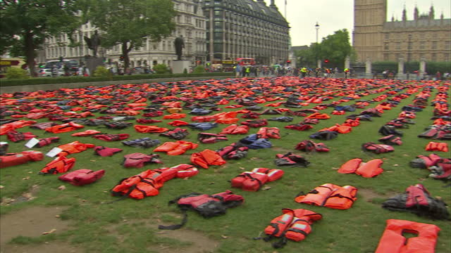 exterior shots of hundreds of life jackets laid out at parliament square green in protest and to put pressure on the uk to do more to help solve the... - flytväst bildbanksvideor och videomaterial från bakom kulisserna
