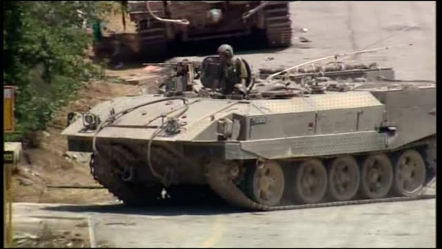 Exterior shots of IDF troops tanks and military vehicles gathered on the Lebanese border with distant explosions audiable as Israeli military...