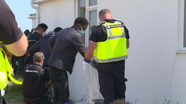 exterior shots of illegal immigrants being searched by british police and uk border force officer's on 20th july 2021 dover, united kingdom. - kent england bildbanksvideor och videomaterial från bakom kulisserna