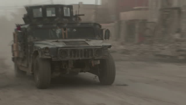 exterior shots of iraqi army vehicles driving down street shot of child holding iraqi flag and shots of locals walking around street with rubble... - iraqi flag stock videos and b-roll footage