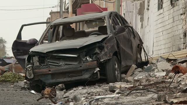 Exterior shots of Iraqi helicopter flying over Mosul shooting at Islamic State ground targets Exterior shots of burnt out car from suicide bomb...