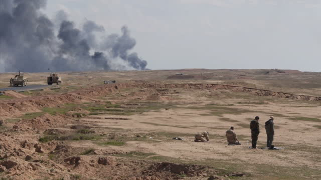 vídeos de stock, filmes e b-roll de exterior shots of iraqi military troops and iraqi shia troops of the badr army militia taking a break and in prayers on the frontline working... - poço de petróleo
