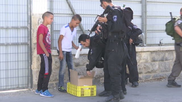 Exterior shots of Israeli police and soldiers at a checkpoint in East Jerusalem searching two young Palestinian boys before they pass through the...