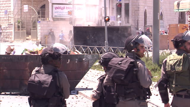 exterior shots of israeli police in an east jerusalem street facing a crowd of palestinian youths throwing rocks as they retaliate by firing smoke or... - east jerusalem stock videos and b-roll footage