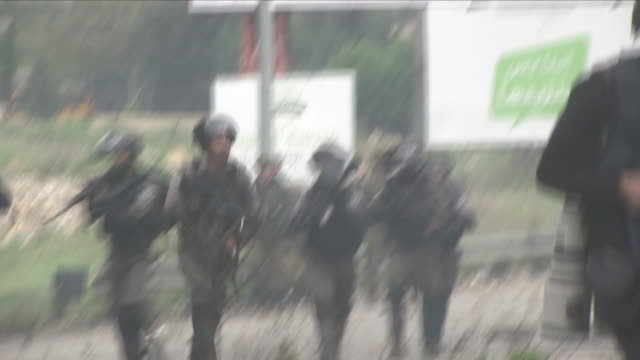 exterior shots of israeli security personnel advancing towards palestinian protesters and taking up positions on a road near the gaza-israel... - 2018年ガザ地区国境抗議点の映像素材/bロール