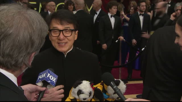 exterior shots of jackie chan speaking briefly to reporters on the red carpet about the cuddly panda toys he is carrying to promote conservation, and... - jackie chan stock videos & royalty-free footage