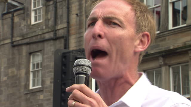 vídeos de stock e filmes b-roll de exterior shots of jim murphy, shadow secretary of state for international development, campaigning in the grassmarket on a red crate at martyr's... - 2014