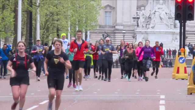 exterior shots of joggers crossing the finish line on constitution hill and completing the 'finish for matt' race including shots of crowds... - london marathon stock videos & royalty-free footage