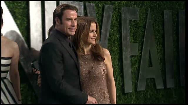 exterior shots of john travolta and wife kelly preston posing for photos on red carpet at vanity fair party. vanity fair party on february 24, 2013... - ehefrau stock-videos und b-roll-filmmaterial
