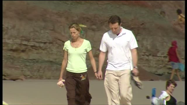 exterior shots of kate and gerry mccann walking on a beach in portugal after the disappearance of their daughter madeleine on may 13, 2007 in lisbon,... - gerry mccann stock-videos und b-roll-filmmaterial