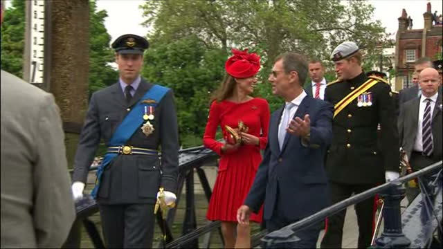 Exterior shots of Kate Middleton Duchess of Cambridge in red dress and matching hat along with Prince William Harry both in full military uniform...