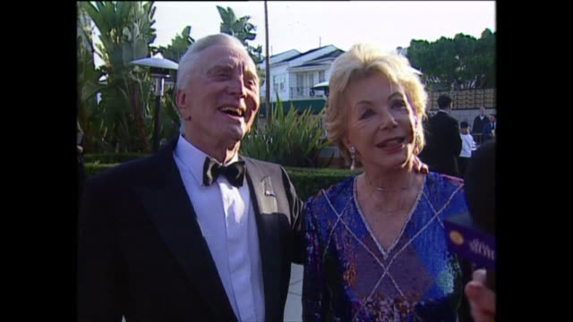 exterior shots of kirk douglas and wife anne buydens speaking to the press on the red carpet for the 71st academy awards at the dorothy chandler... - 俳優 カーク・ダグラス点の映像素材/bロール