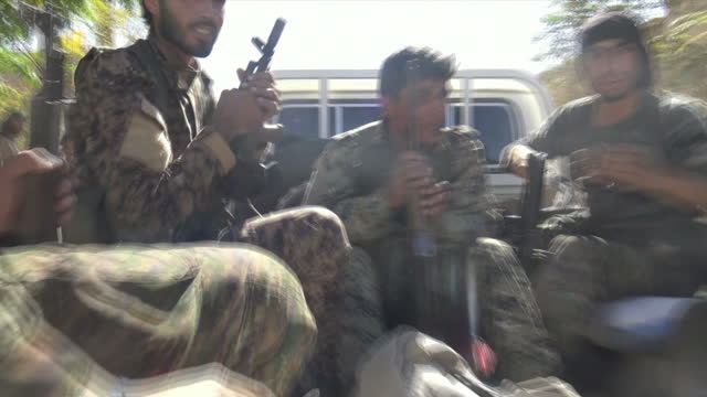 vídeos de stock, filmes e b-roll de exterior shots of kurdish ypg soldiers with guns in pickup trucks after the fall of raqqa on 17 october 2017 in raqqa syria - curdo